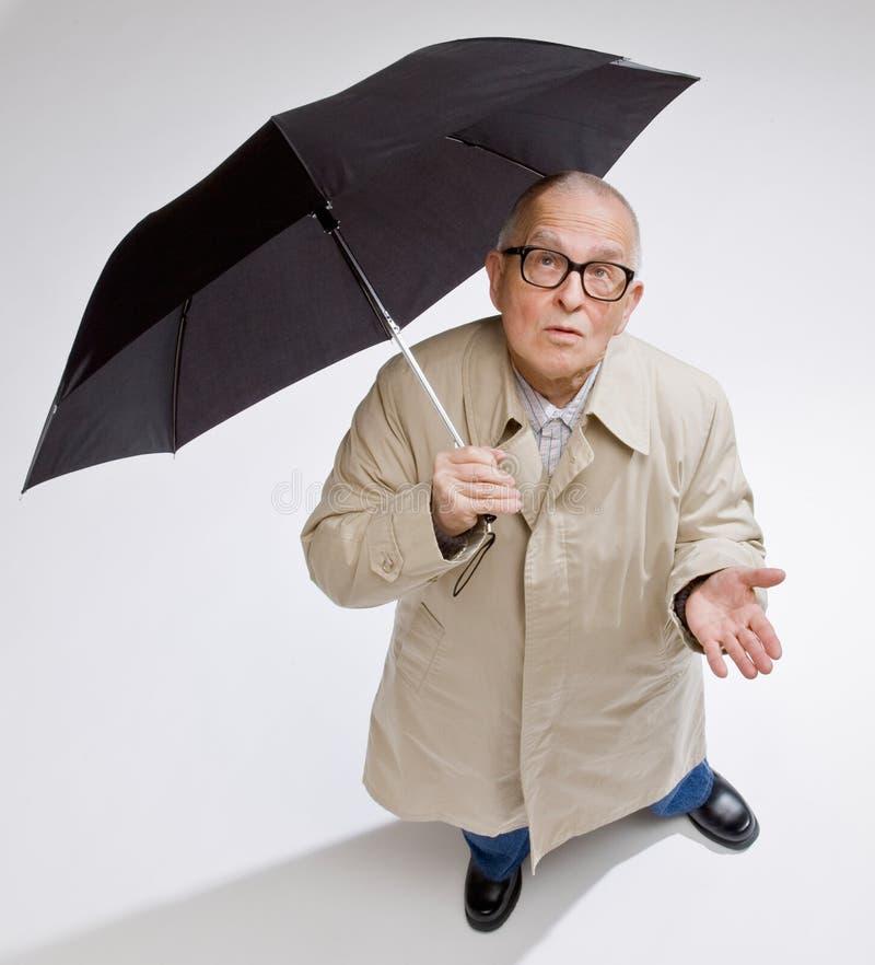 Homme dans le parapluie de fixation d'imperméable vérifiant la pluie photo stock