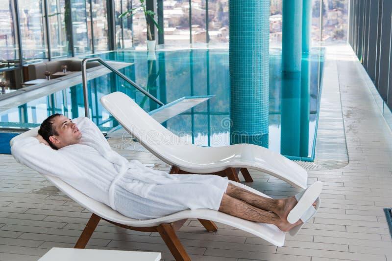 Homme dans le peignoir détendant près de la piscine d'intérieur dans la station thermale de luxe images libres de droits