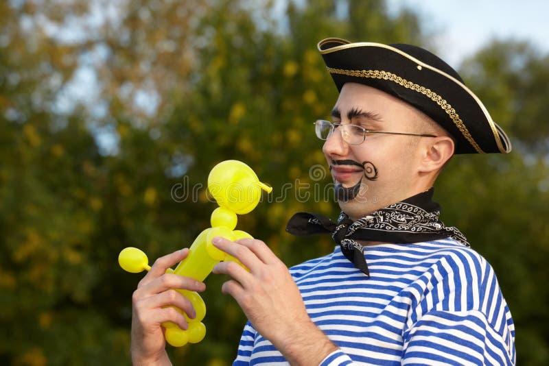 Homme dans le procès de pirate regardant l'air-ballon de chienchien. photographie stock libre de droits