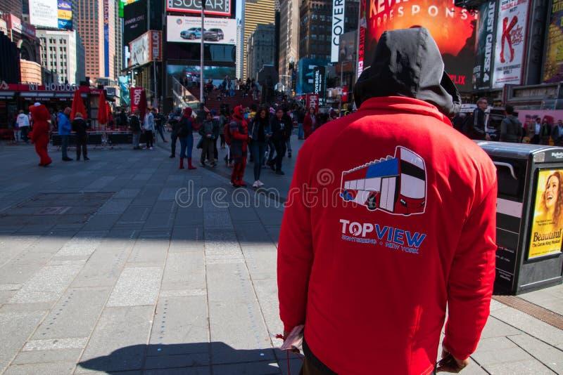 Homme dans le pull molletonné rouge dans le Times Square Manhattan New York vendant des billets pour l'houblon sur l'houblon out photos stock