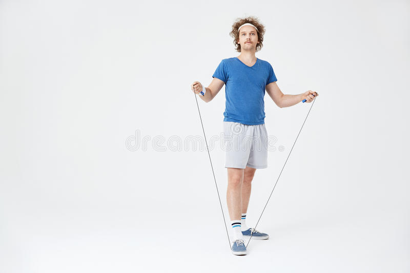 Homme dans le rétro équipement de sport tenant la corde à sauter à disposition image libre de droits