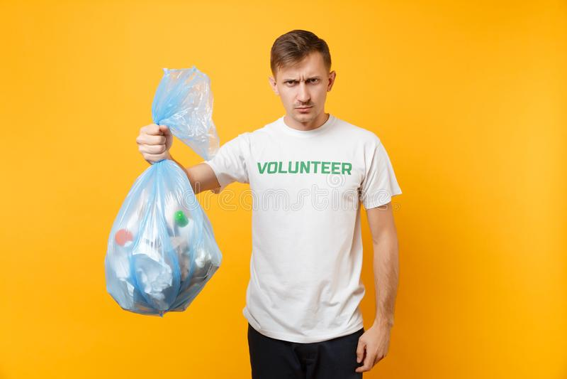 Homme dans le sac de déchets volontaire de prise de T-shirt d'isolement sur le fond jaune Grâce libre volontaire de charité d'aid photo libre de droits