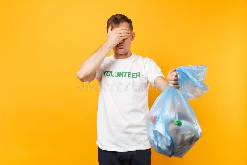Homme dans le sac de déchets volontaire de prise de T-shirt d'isolement sur le fond jaune Grâce libre volontaire de charité d'aid image libre de droits