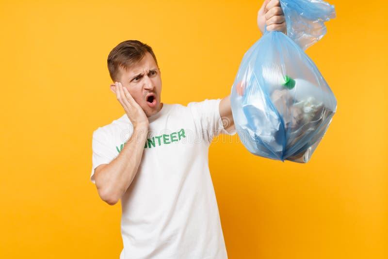 Homme dans le sac de déchets volontaire de prise de T-shirt d'isolement sur le fond jaune Grâce libre volontaire de charité d'aid photos libres de droits