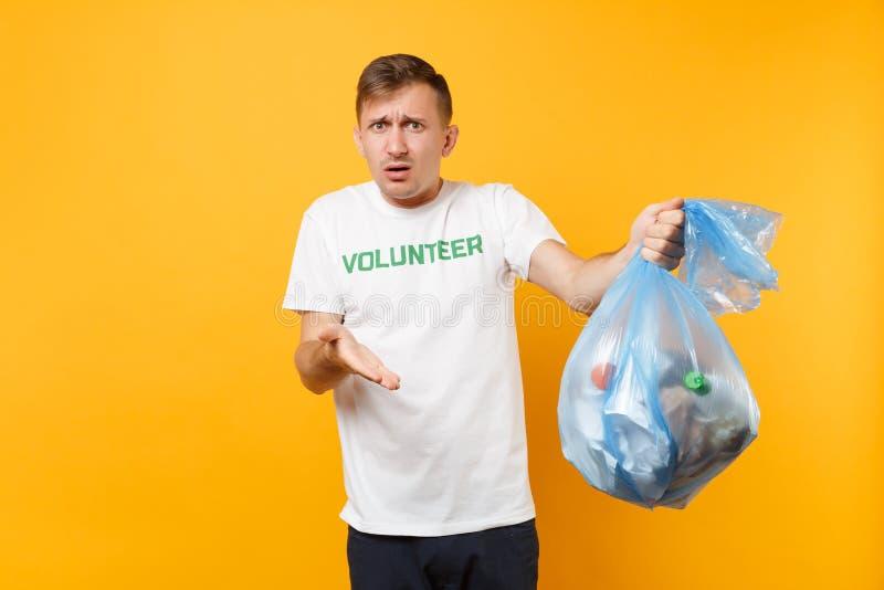Homme dans le sac de déchets volontaire de prise de T-shirt d'isolement sur le fond jaune Grâce libre volontaire de charité d'aid photographie stock
