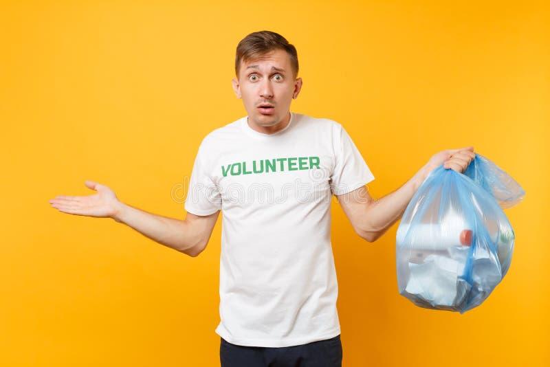 Homme dans le sac de déchets volontaire de prise de T-shirt d'isolement sur le fond jaune Grâce libre volontaire de charité d'aid photographie stock libre de droits