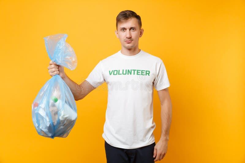 Homme dans le sac de déchets volontaire de prise de T-shirt d'isolement sur le fond jaune Grâce libre volontaire de charité d'aid images stock
