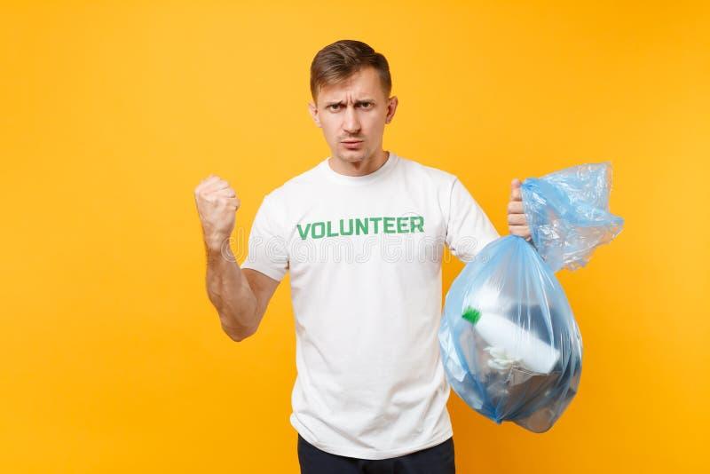 Homme dans le sac de déchets volontaire de prise de T-shirt d'isolement sur le fond jaune Grâce libre volontaire de charité d'aid photo stock