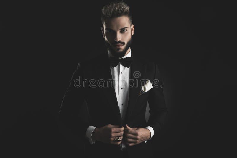 Homme dans le smoking ajustant sa veste de salon avec les deux mains images stock