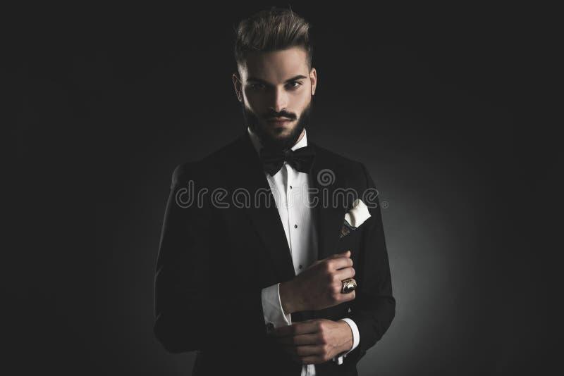 Homme dans le smoking fixant sa douille photos stock