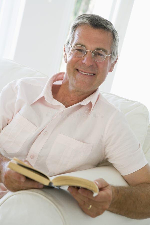 Homme dans le sourire de livre de relevé de salle de séjour images stock