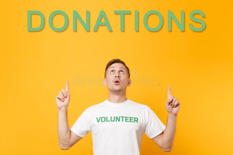 Homme dans le T-shirt blanc avec le volontaire écrit de vert d'inscription recherchant, dirigeant des doigts sur des donations de photographie stock libre de droits