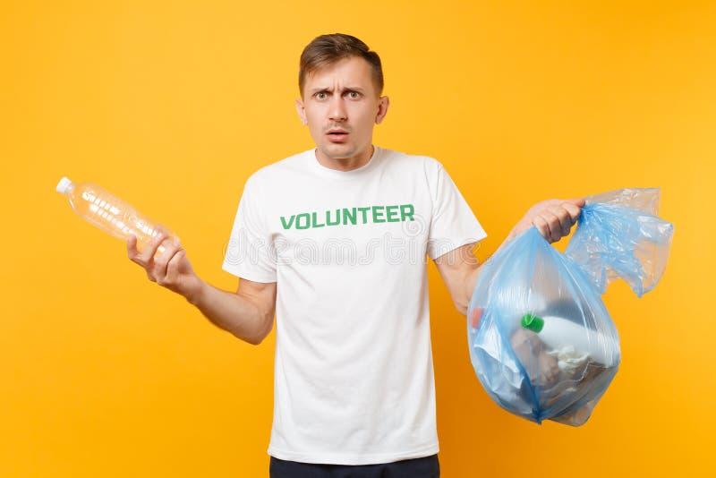 Homme dans le volontaire de T-shirt, sac de déchets d'isolement sur le fond jaune Aide libre volontaire d'aide, grâce de charité photo stock