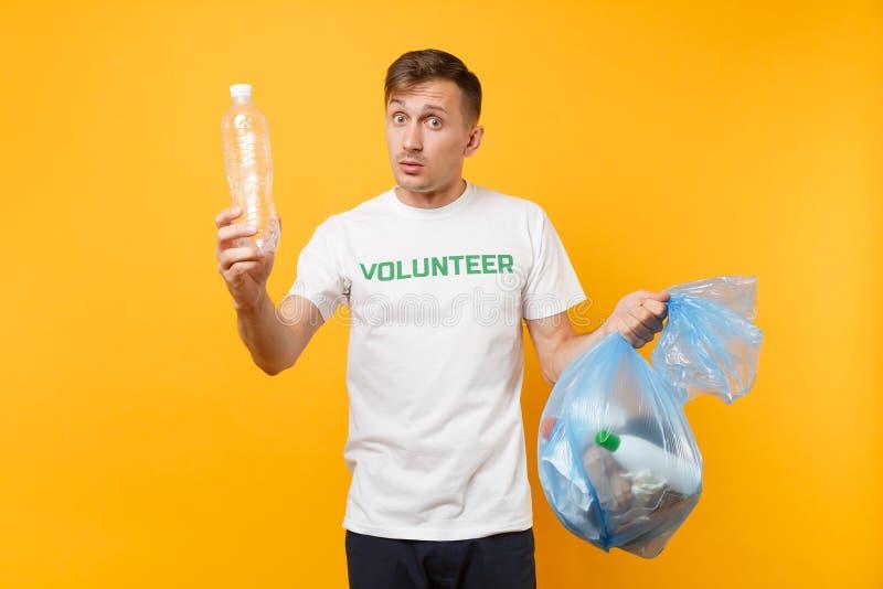 Homme dans le volontaire de T-shirt, sac de déchets d'isolement sur le fond jaune Aide libre volontaire d'aide, grâce de charité image libre de droits