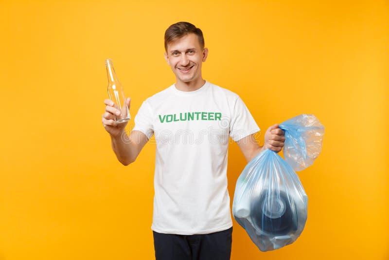Homme dans le volontaire de T-shirt, sac de déchets d'isolement sur le fond jaune Aide libre volontaire d'aide, grâce de charité photographie stock