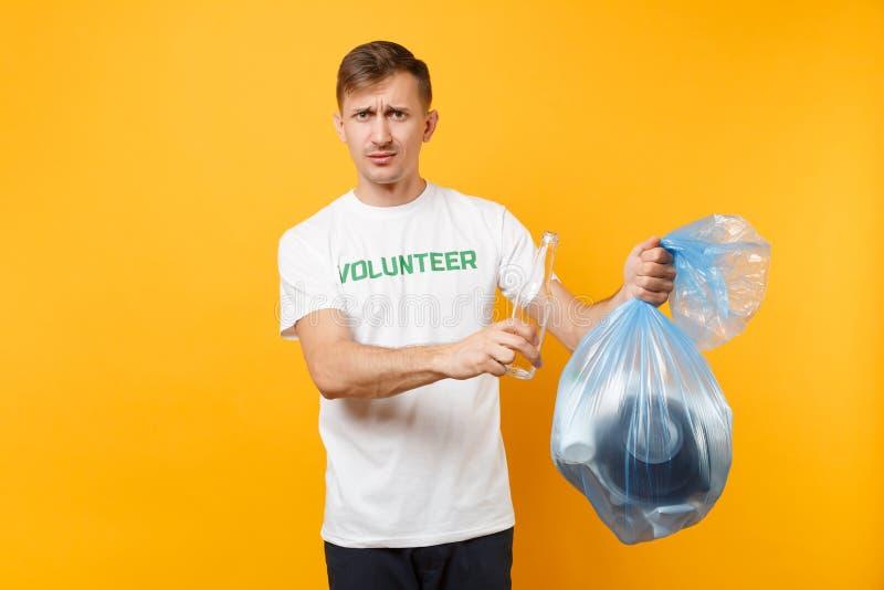 Homme dans le volontaire de T-shirt, sac de déchets d'isolement sur le fond jaune Aide libre volontaire d'aide, grâce de charité photos libres de droits
