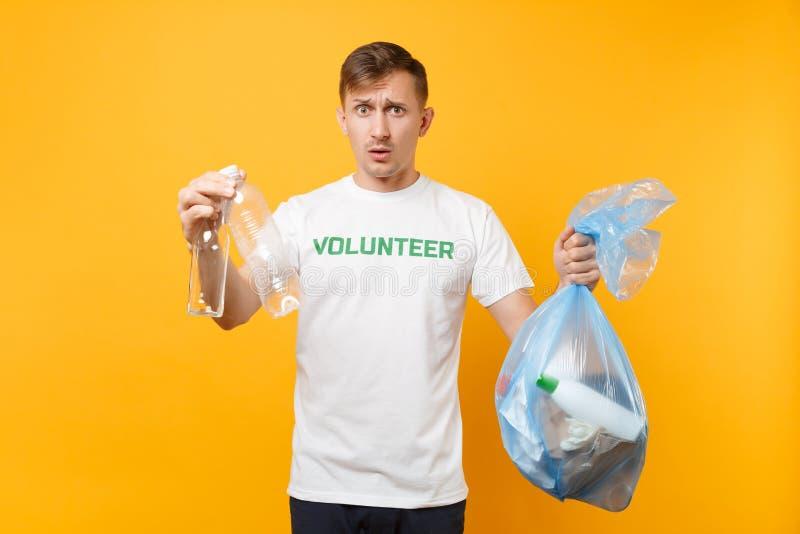 Homme dans le volontaire de T-shirt, sac de déchets d'isolement sur le fond jaune Aide libre volontaire d'aide, grâce de charité photo libre de droits