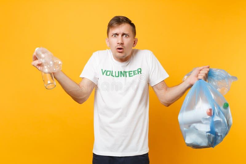 Homme dans le volontaire de T-shirt, sac de déchets d'isolement sur le fond jaune Aide libre volontaire d'aide, grâce de charité images libres de droits