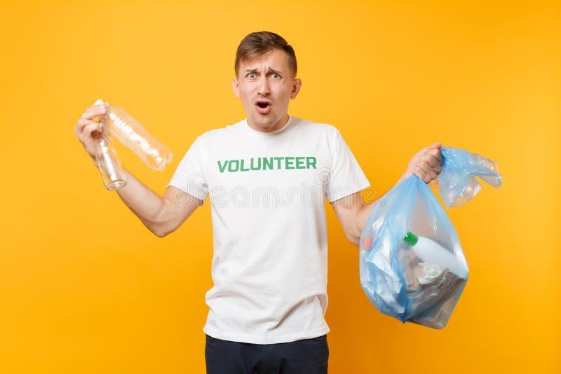 Homme dans le volontaire de T-shirt, sac de déchets d'isolement sur le fond jaune Aide libre volontaire d'aide, grâce de charité photographie stock libre de droits
