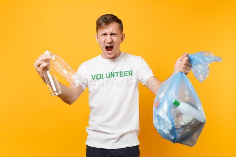 Homme dans le volontaire de T-shirt, sac de déchets d'isolement sur le fond jaune Aide libre volontaire d'aide, grâce de charité image stock