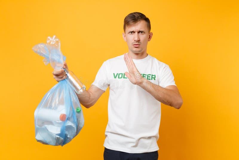 Homme dans le volontaire de T-shirt, sac de déchets d'isolement sur le fond jaune Aide libre volontaire d'aide, grâce de charité photos stock