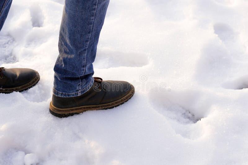 Homme dans les bottes brunes et des blues-jean desided pour faire la première étape à l'obscurité sur la neige Copiez l'espace Pr photo stock