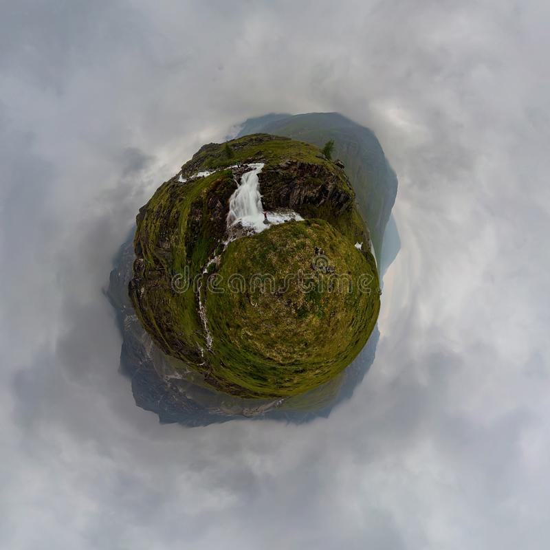 Homme dans les supports rouges sous la cascade sur la roche noire en montagnes le jour pluvieux nuageux Petite planète minuscule  images libres de droits