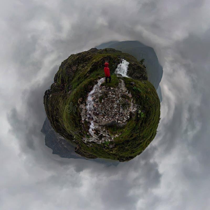 Homme dans les supports rouges sous la cascade sur la roche noire en montagnes le jour pluvieux nuageux Petite plan?te minuscule  image libre de droits