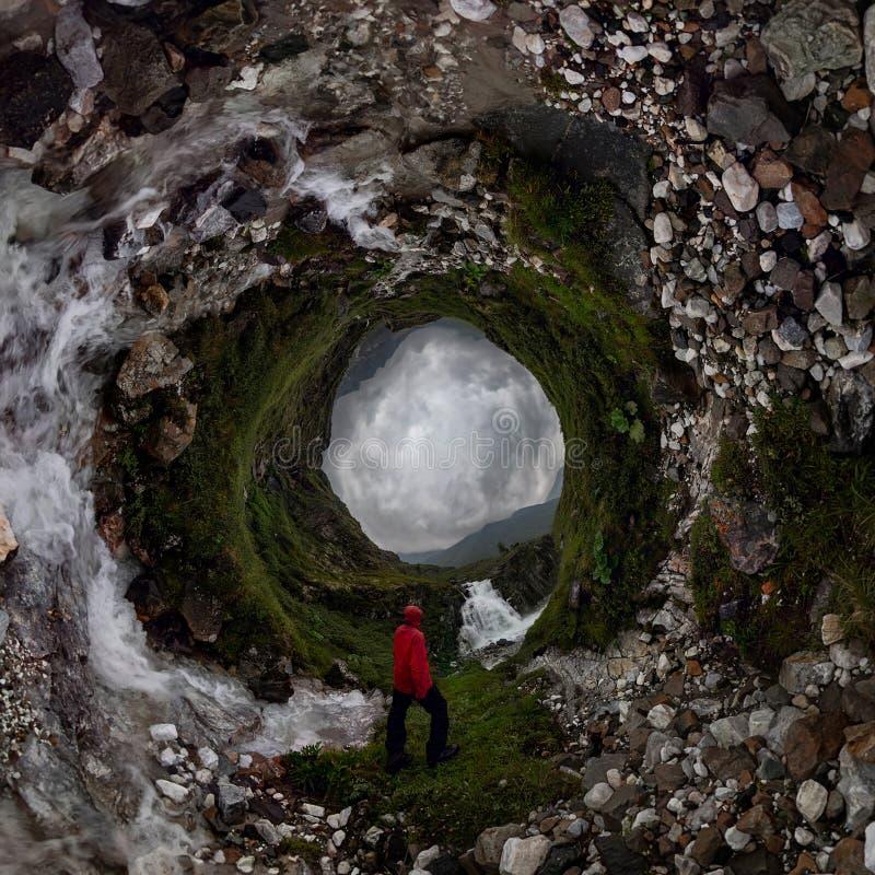 Homme dans les supports rouges sous la cascade sur la roche noire en montagnes le jour pluvieux nuageux Petite plan?te minuscule  images libres de droits