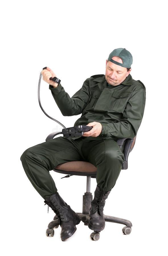 Homme dans les vêtements de travail se reposant avec le téléphone. photographie stock