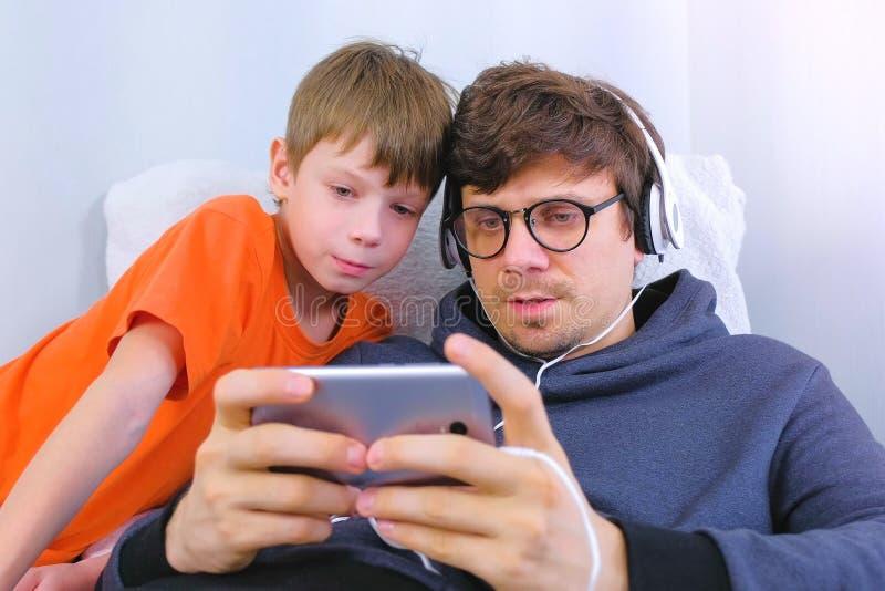 Homme dans les verres et des ?couteurs jouant un jeu dans le smartphone avec son fils Le Gamer d?tendent image libre de droits