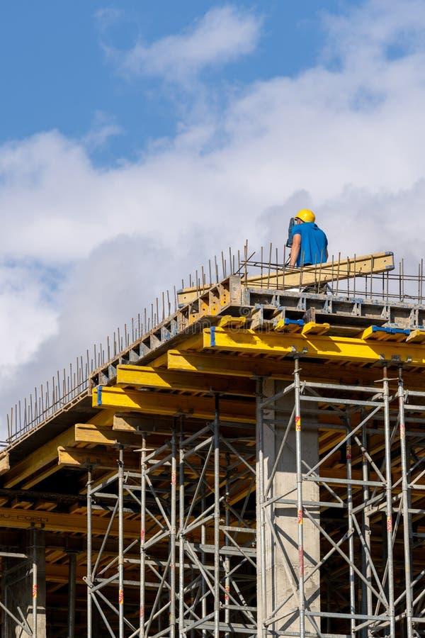 Homme dans se protéger pour porter le regard par l'arpenteur sur l'élément de bâtiment image stock