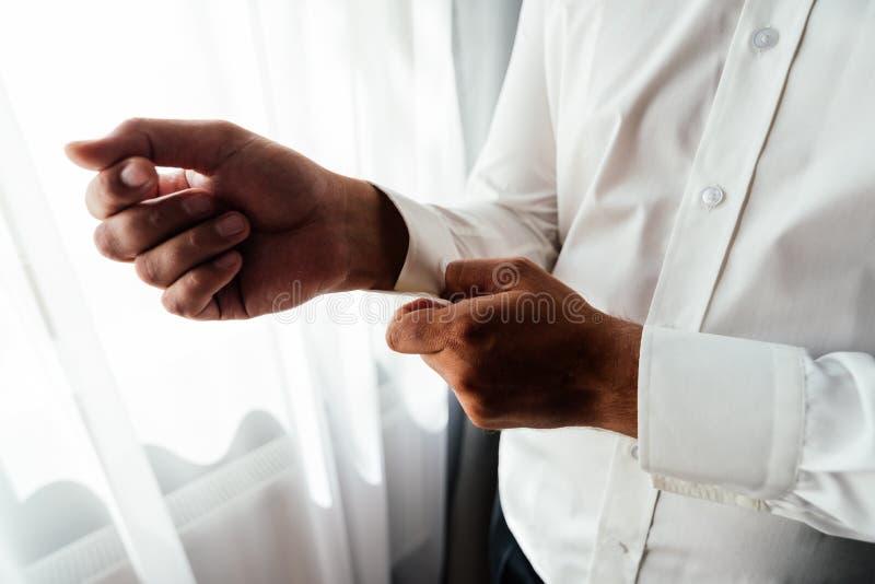 Homme dans un boutonnage de chemise blanc un bouton sur la manchette de chemise photos stock
