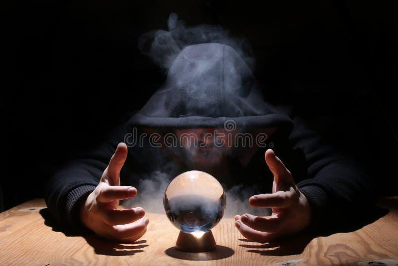 Homme dans un capot noir avec la boule cristal image stock