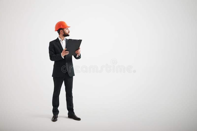 Homme dans un casque noir de costume et de construction regardant au côté photographie stock libre de droits