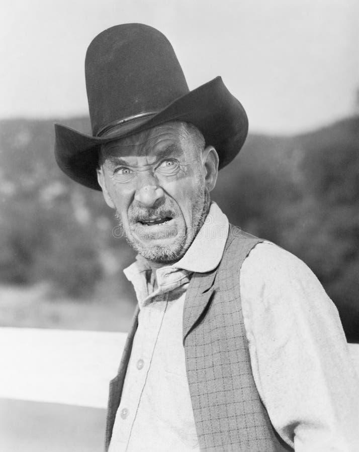 Homme dans un chapeau de cowboy semblant fâché (toutes les personnes représentées ne sont pas plus long vivantes et aucun domaine photographie stock libre de droits