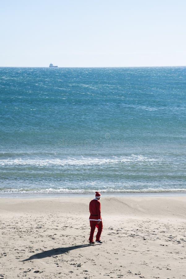 Homme dans un costume de Santa marchant sur le sable d'une plage photographie stock