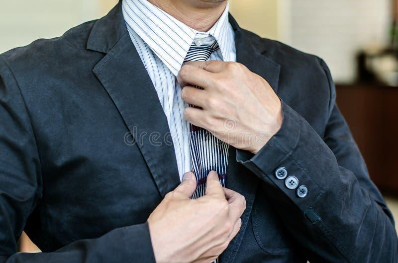 Homme dans un costume fixant le sien lien images stock