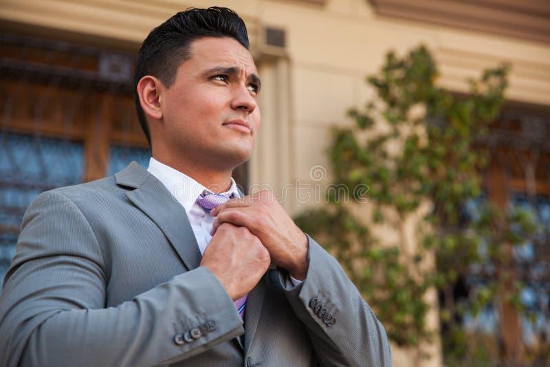 Homme dans un costume fixant le sien lien photographie stock