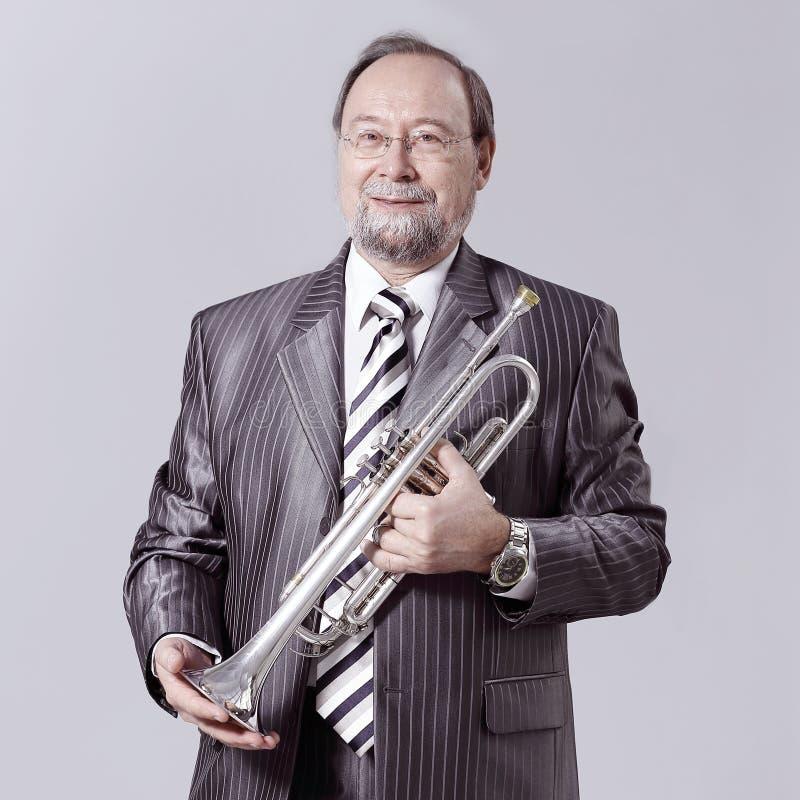 Homme dans un costume gris avec une trompette photographie stock libre de droits