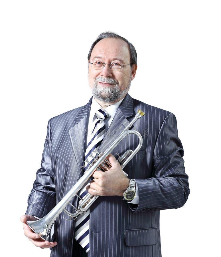Homme dans un costume gris avec une trompette photo libre de droits