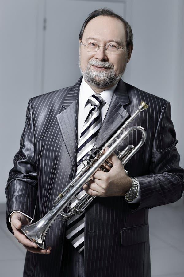 Homme dans un costume gris avec une trompette photographie stock