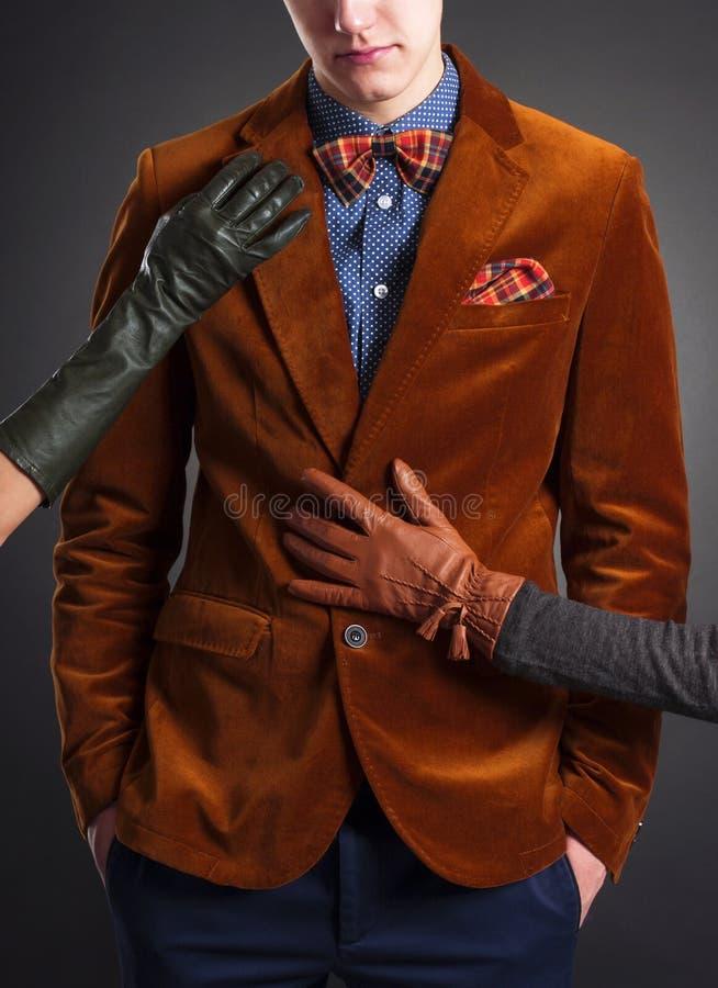 Homme dans un costume rouge et des mains des femmes photographie stock
