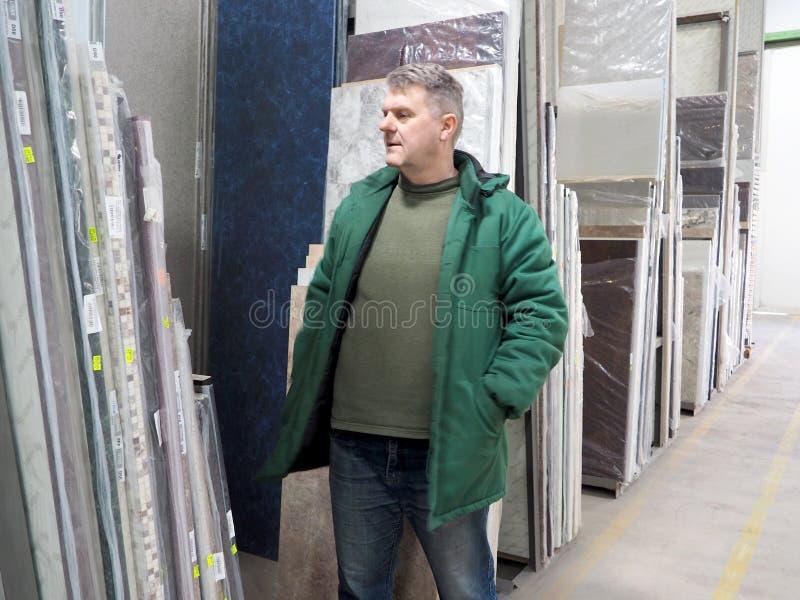 Homme dans un entrepôt de matériaux de construction photographie stock libre de droits