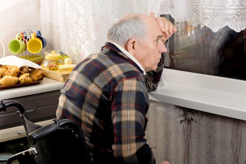Homme dans un fauteuil roulant scrutant par une fenêtre image libre de droits