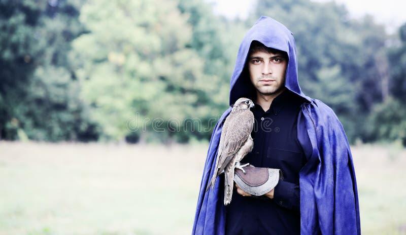 Homme dans un imperméable avec un faucon image stock