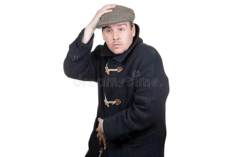 Homme dans un manteau gris-foncé tenant le chapeau image libre de droits