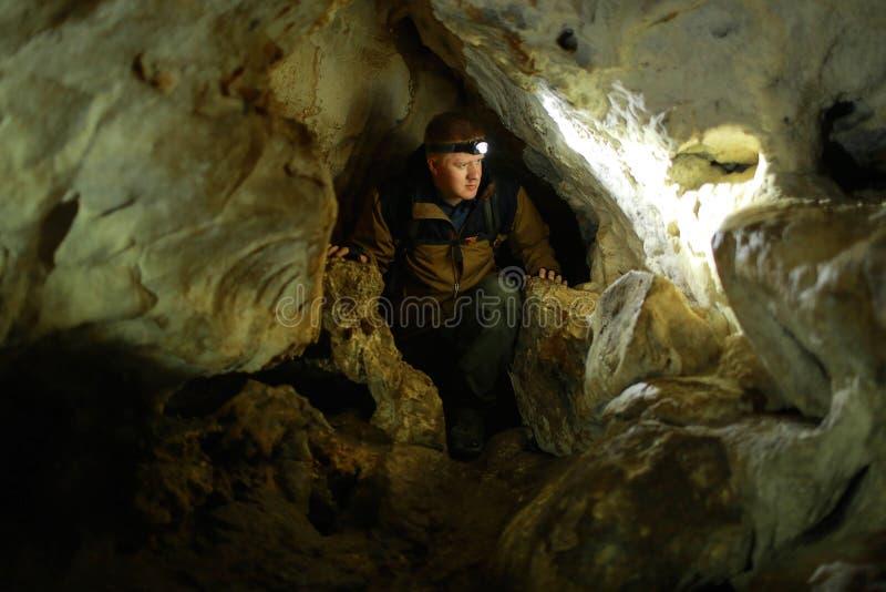 Homme dans un passage étroit dans une caverne de karst photographie stock