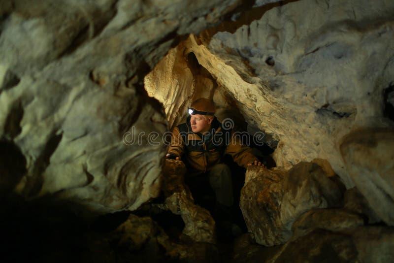 Homme dans un passage étroit dans une caverne de karst images stock