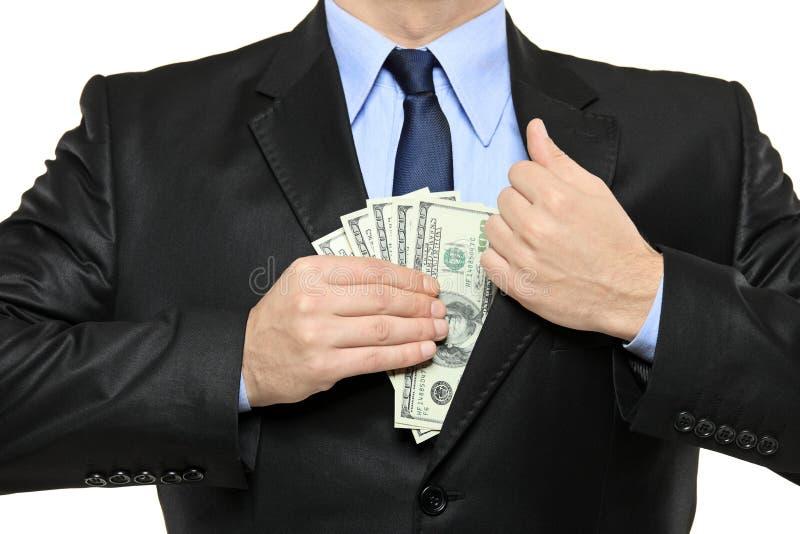 Homme dans un procès mettant l'argent dans sa poche photo stock